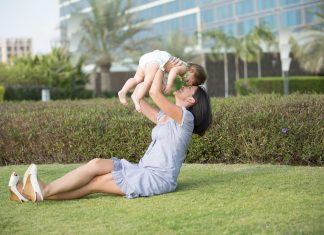 Mother with child in air